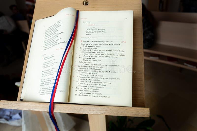 Öppnad bibelbok i franskt språk på ställning royaltyfri fotografi
