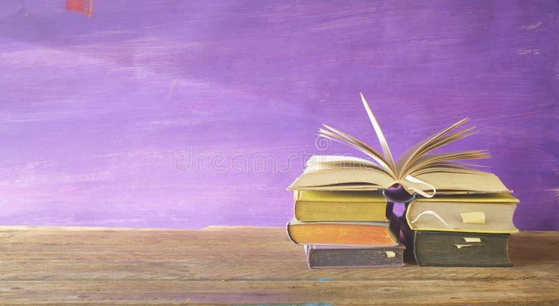 Öppnad bok på en hög av böcker, arkivfoton