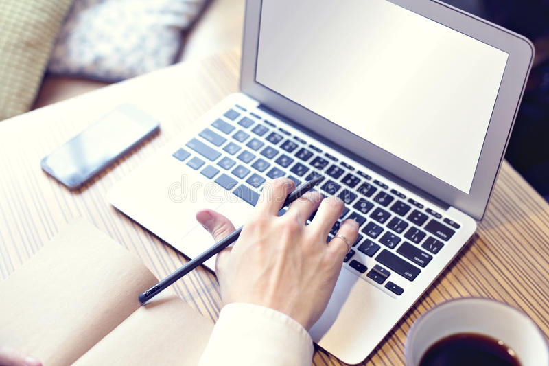 Öppnad dator, affärsman som dricker kaffe och arbete på bärbara datorn, mobiltelefon, handstil, närbildassistent royaltyfri bild