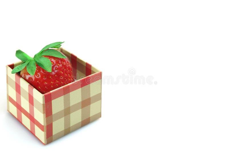 Öppnad gåvaask med söt jordgubbefrukt som isoleras på vit arkivbild