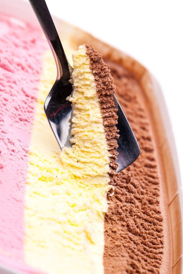 Öppnad glassstorförpackning med 3 olika kulöra glasssorter en sked fotografering för bildbyråer