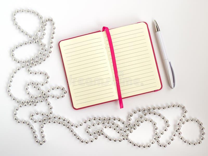 Öppnad notepad med fodrat papper, den vita kulspetspennan och att försilvra den kulöra pärljulgirlanden på en ljus bakgrund, fest arkivfoto