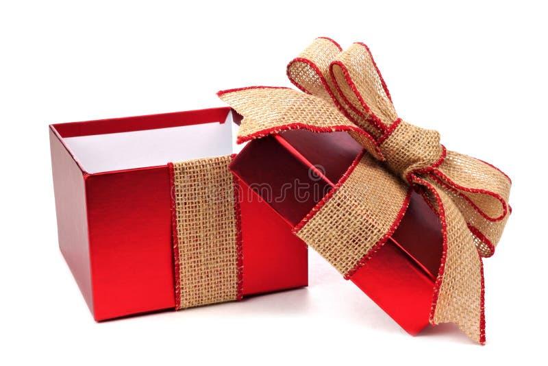 Öppnad röd gåvaask med den lantliga det säckvävpilbågen och bandet royaltyfria bilder