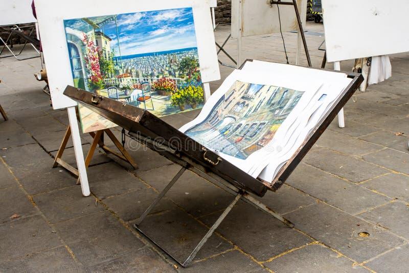 Öppnad staffliportfölj med arbete av en gatakonstnär inom Utställning var målare säljer deras målningar royaltyfri foto