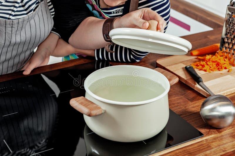 Öppnad vit kastrull med träpennor på den svarta ugnen Laga mat en soppa - vattenkoka, kontroll och förberedelse kvinna för hand s royaltyfri fotografi