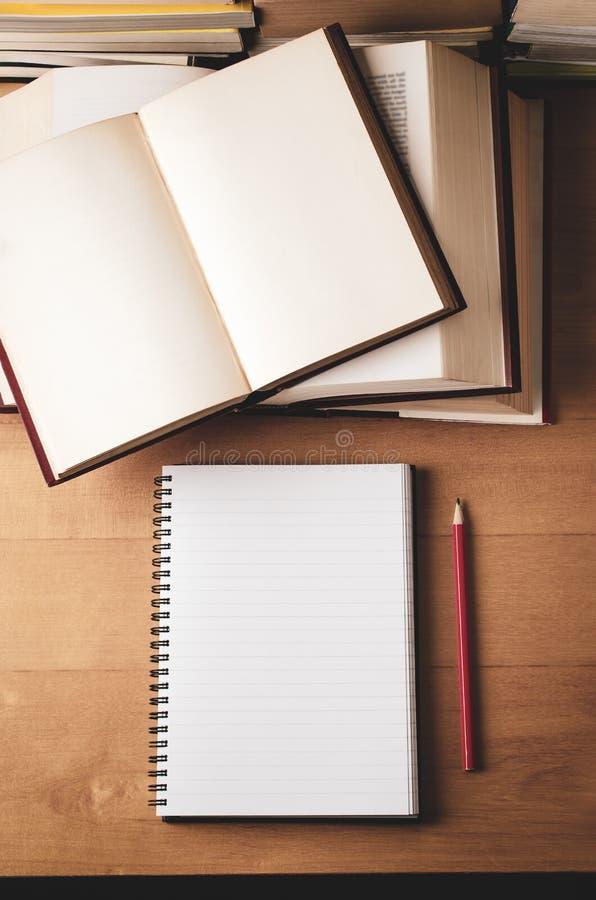Öppnade bildande böcker som staplas på skrivbordet från över fotografering för bildbyråer
