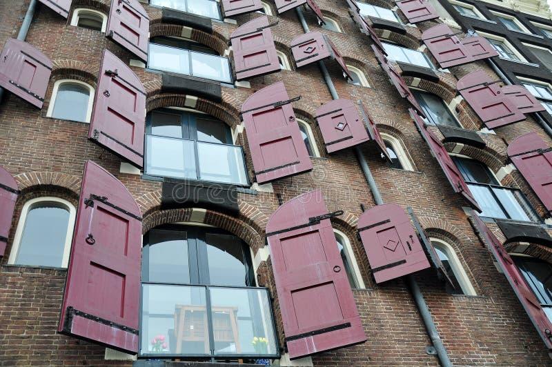 Öppnade fönster av lägenheter med röda slutare, Amsterdam, Nederländerna royaltyfri foto
