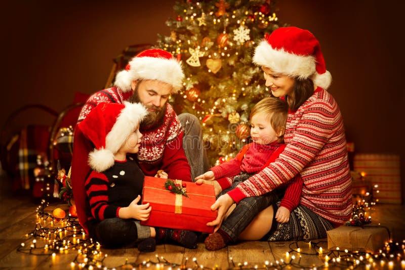 Öppnande gåva för julfamilj, Xmas-träd och gåvor, lycklig fader Mother Child och Baby i Red Hat royaltyfri bild