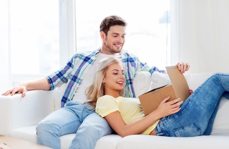Öppnande jordlottask för lyckliga par hemma royaltyfri foto