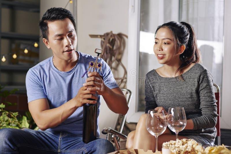 Öppnande vin för ung asiatisk man arkivbilder