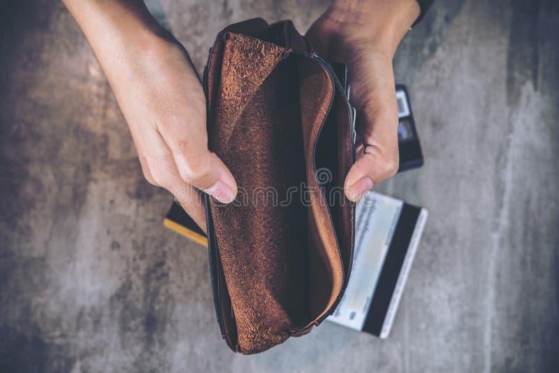 Öppnar händer för man` ett s en tom läderplånbok med kreditkortar på tabellen arkivbild