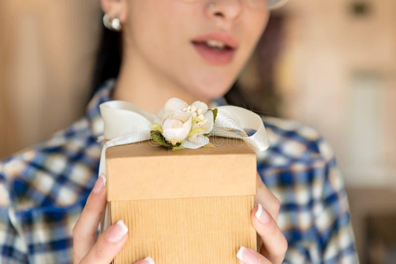 Öppning för gåvaask i lyckliga kvinnahänder arkivfoto