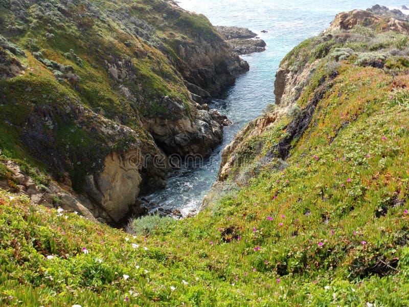 Öppningen längs Kalifornien de kust- klipporna och små kiselstenar sätter på land - huvudväg 1 för vägturen ner arkivfoto