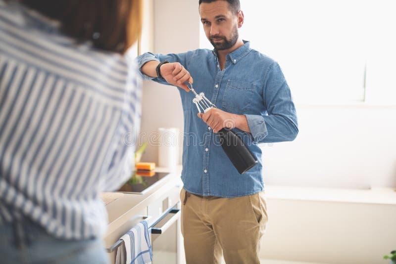 Öppningsflaska för ung man av vin, medan se damen royaltyfria bilder