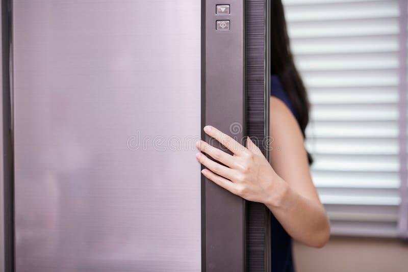 Öppningskylskåp för ung kvinna, closeup royaltyfri fotografi