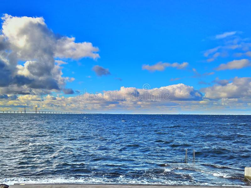 Öresund Bridge from Malmö beach at daytime. A daytime HDR shot of the sea with the Öresund bridge to the left. Shot from Västra Hamnen in Malm royalty free stock image