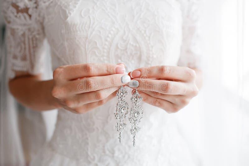 örhänge i brud- händer Härlig brölloptillbehör datum Höstferie arkivbild
