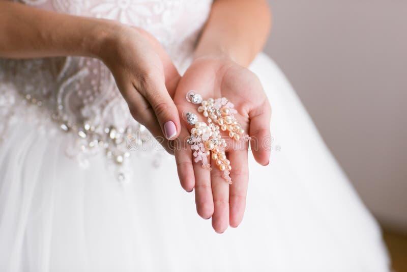 örhänge i brud- händer Härlig brölloptillbehör datum Höstferie arkivbilder