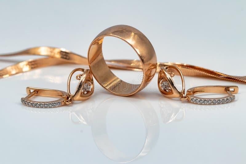 Örhängen med dansdiamanter, den guld- cirkeln och den guld- kedjan arkivbilder