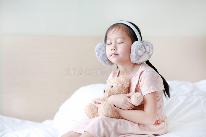 Öronskydd för vinter för stängd liten asiatisk barnflicka för ögon bärande och omfamna nallebjörnen, medan sitta på sängen hemma arkivfoto