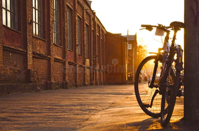Örtlich festgelegtes Fahrrad in der Reflexion geparkt am Bürgersteig stockfotografie