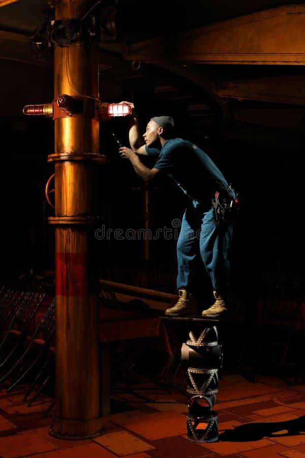 Örtlich festgelegtes Licht der lustigen Elektrikerarbeitskraft stockfoto