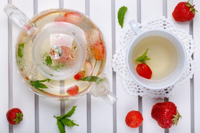 Örtte med den nya jordgubben och mintkaramellen Varm dryck i exponeringsglastekanna och kopp på det vita magasinet, bästa sikt royaltyfri fotografi