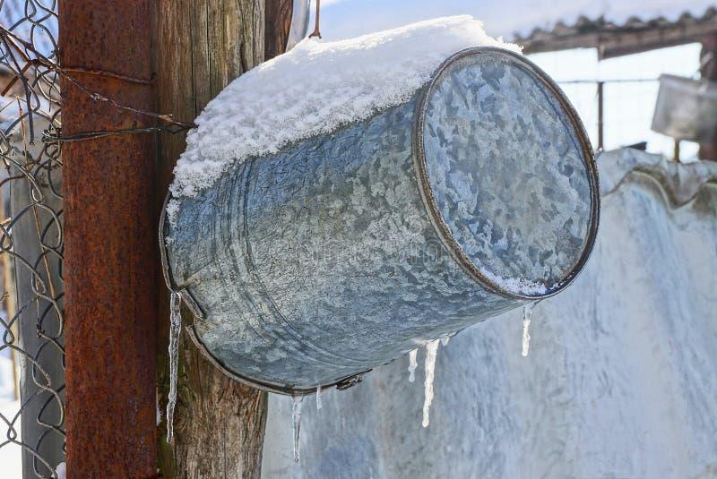 Ösregna att hänga på gatan under snö och istappar arkivfoto