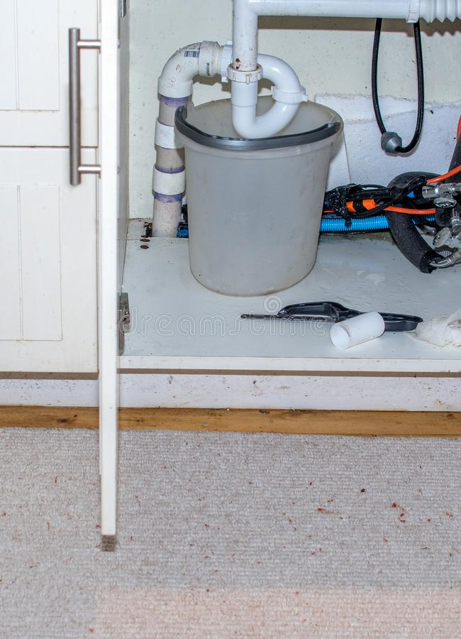 Ösregna under ett rör av en läcka vask arkivfoton