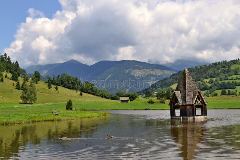 Österreichische Alpen - Kirche im Wasser stockbild
