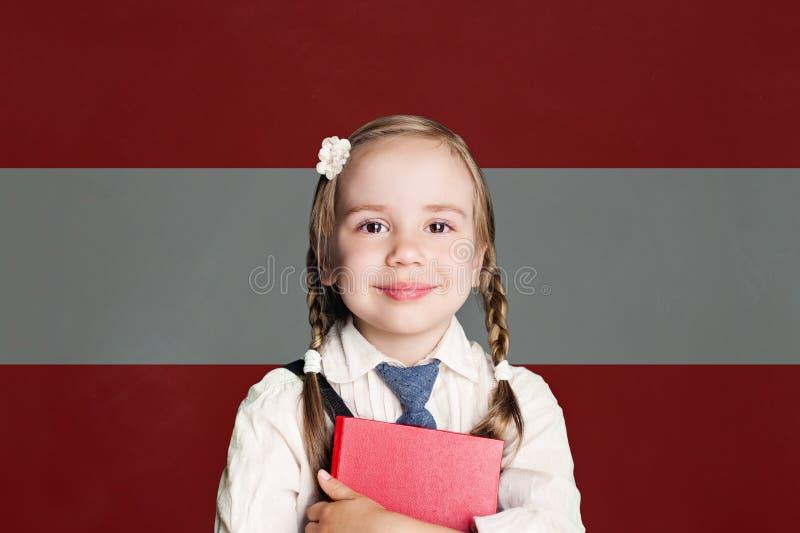Österrike begrepp med liten flickastudenten med boken mot den österrikiska flaggabakgrunden arkivbild