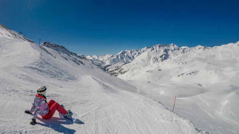 ?sterrike - en snowboardingflicka som beundrar sikten p? h?gv?xta berg arkivbild
