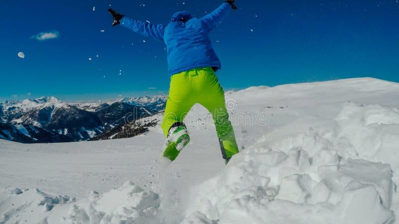 Österrike - Mölltaler Gletscher, man som hoppar I snön royaltyfria bilder