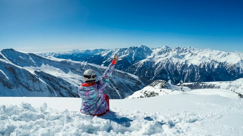 Österrike - Snowboardingflicka som sitter på snön som tycker om sikten royaltyfria bilder