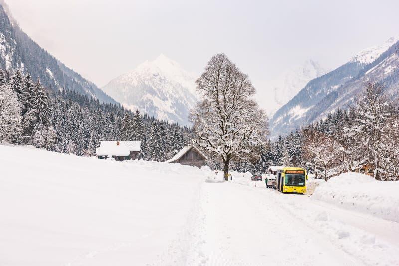 Österrikisk buss och trähus Berg p? bakgrunden Skidar regionen Schladming-Dachstein, det Liezen området, Styria, Österrike royaltyfri foto