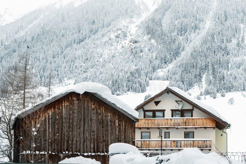 Österrikiska alpina bylandskap med små kalv- och trälador, tallskogsträd och snötäckta berg på royaltyfri bild