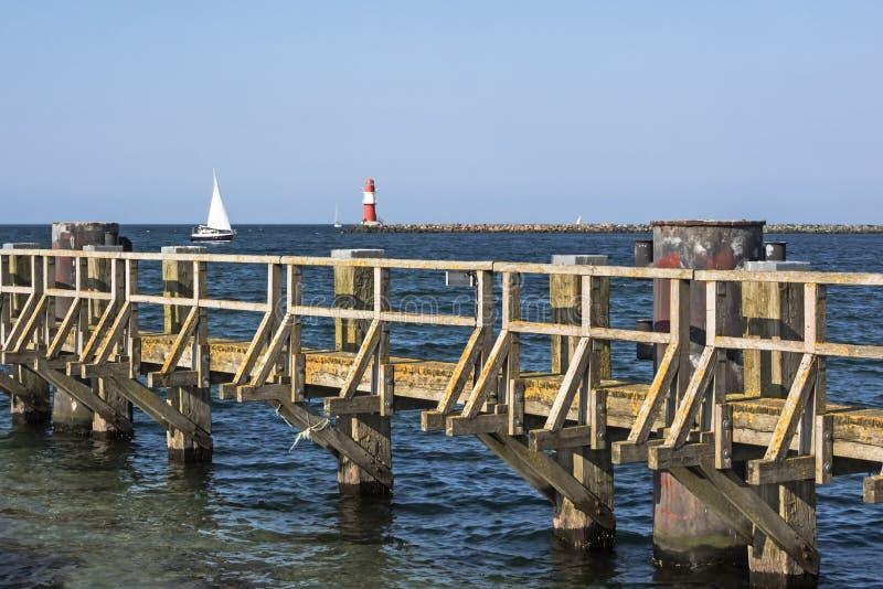 Östersjön med den träpir, fyren och seglingskeppet på Rostock Warnemuende, Tyskland arkivfoton
