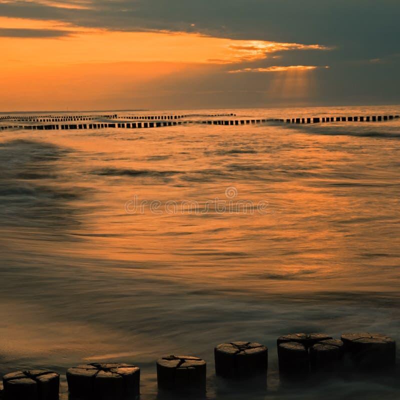 Östersjön med vågbrytare på solnedgången arkivfoton