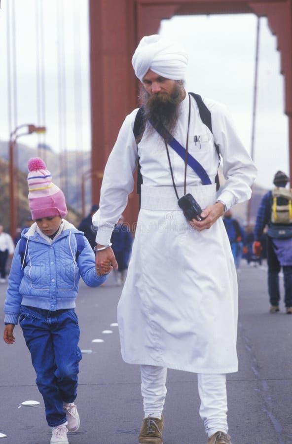 Östliche religiöse Person, die über Golden gate bridge in San Francisco California geht stockbild