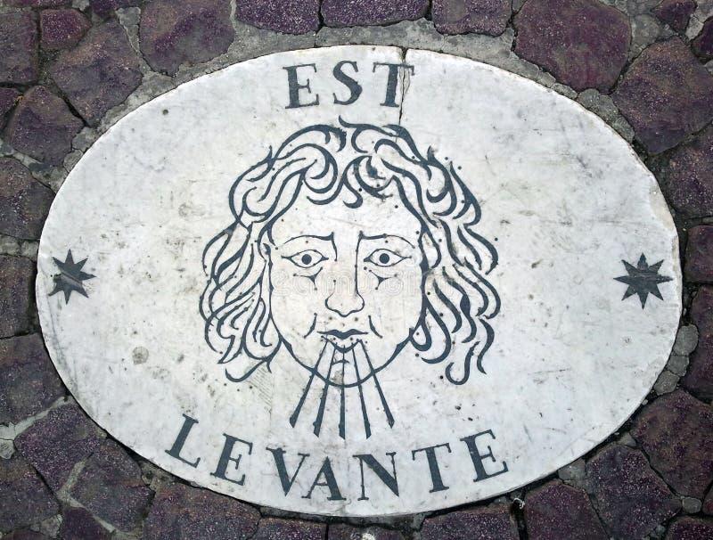 Östlig Est - ett huvud som symboliserar riktningen av vinden En forntida bild på en marmortjock skiva i fyrkant för St Peter ` s  arkivbild
