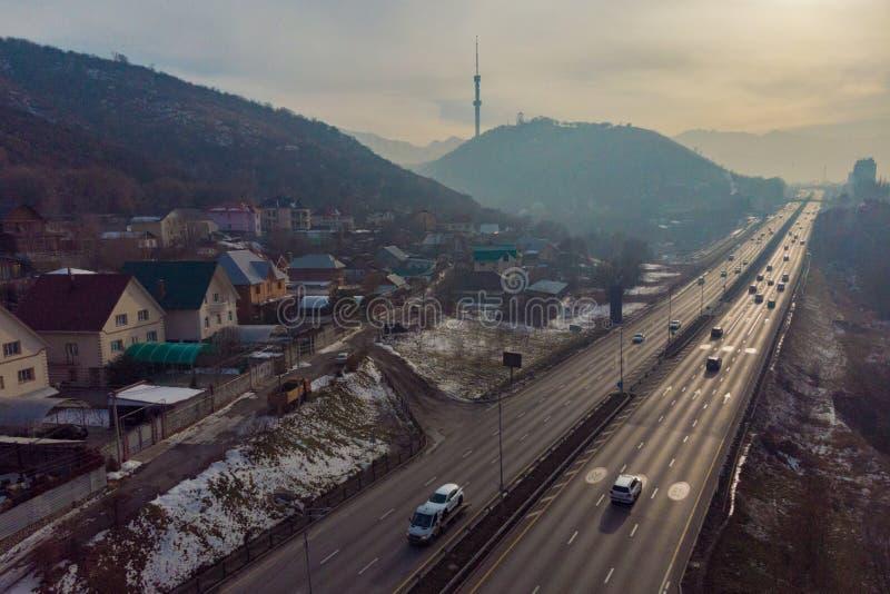 Östlig förbikopplingsväg Almaty stad kazakhstan Berg och TVtorn arkivfoto