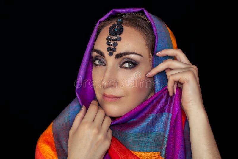 Östlig kvinna i burqa med juvlar på en svart bakgrund royaltyfri fotografi