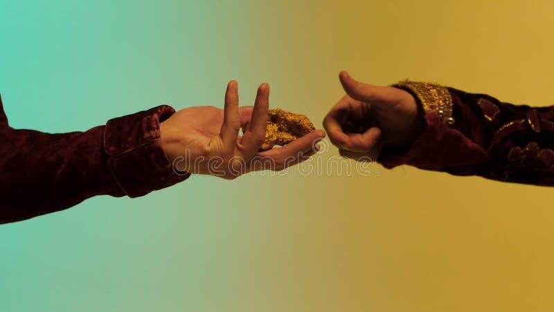 Östlig man som tar ett stycke av den guld- klumpen från en annan man, händer som isoleras på färgglad bakgrund materiel Slut upp  royaltyfria bilder