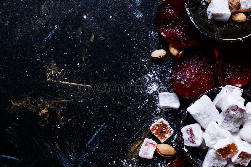 Östliga sötsaker med sockerpulver, pistascher och rosa kronblad, fo fotografering för bildbyråer