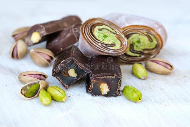 Östliga turkiska sötsaker med pistascher på en vit träbakgrund Chokladgodis med pistasch-, baklava- och pistaschmuttrar arkivbild