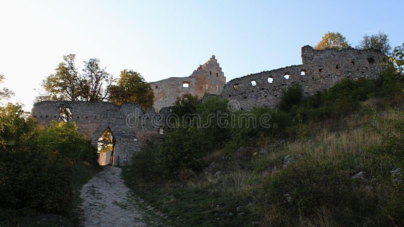 Östliga väggar och den huvudsakliga ingången till fördärvar av den tidiga gotiska slotten Topolcany under tidig nedgångsolnedgång royaltyfria bilder