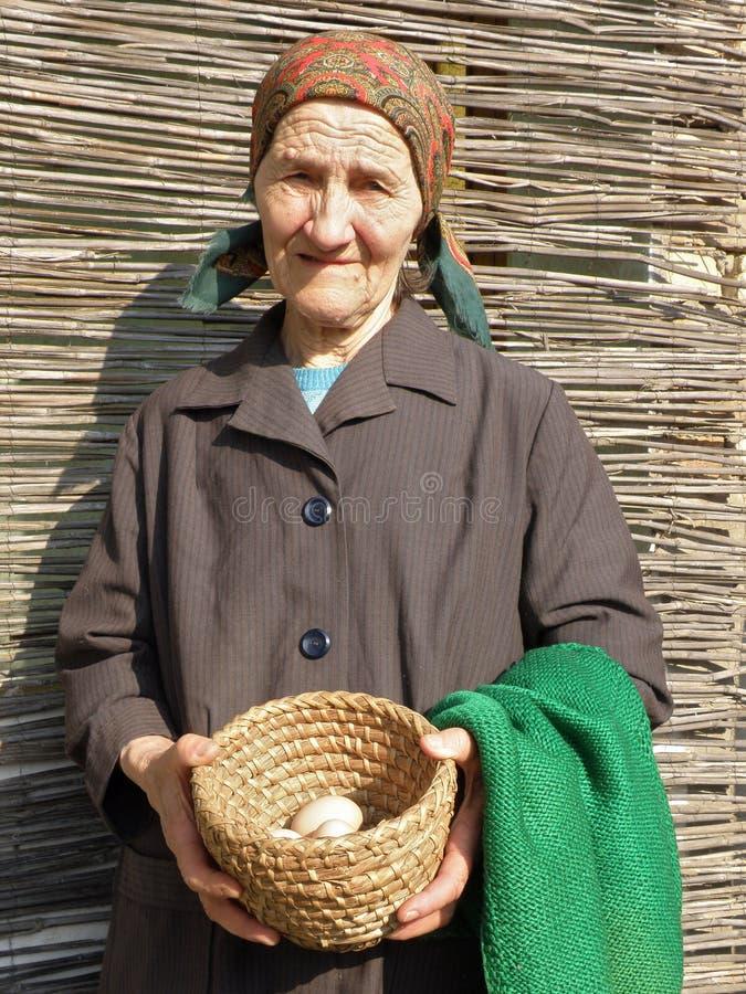 Östligt - hållande ägg för europeisk hög bondekvinna royaltyfri bild