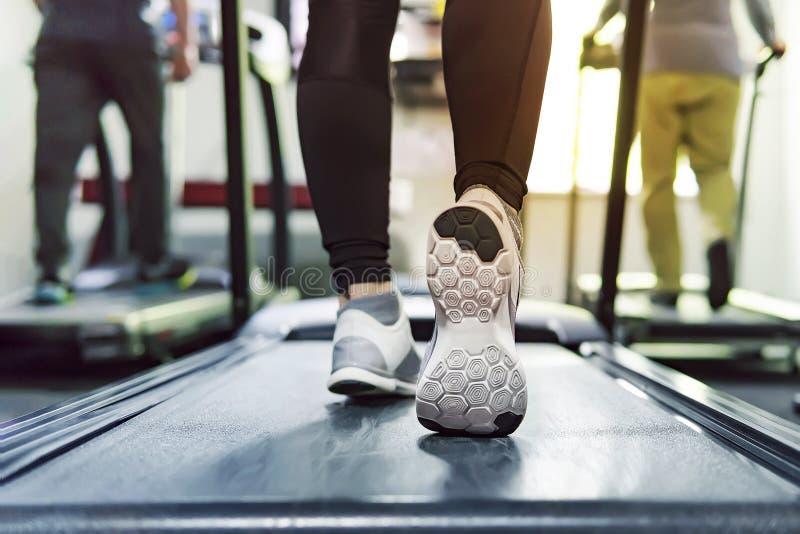 Öva den cardio rinnande genomköraren för trampkvarnen på konditionidrottshallen av kvinnan som tar viktförlust med maskinen som ä royaltyfria foton