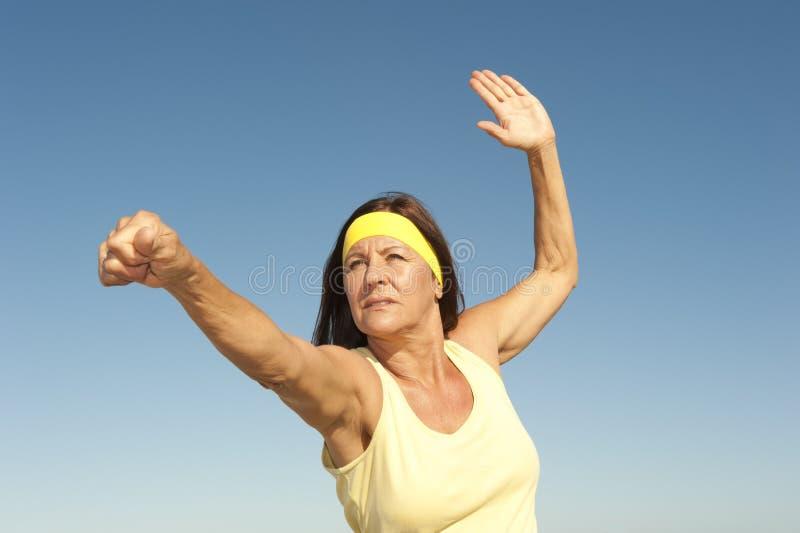 Öva för kvinna för en mitt som åldrigt är utomhus-   royaltyfria bilder