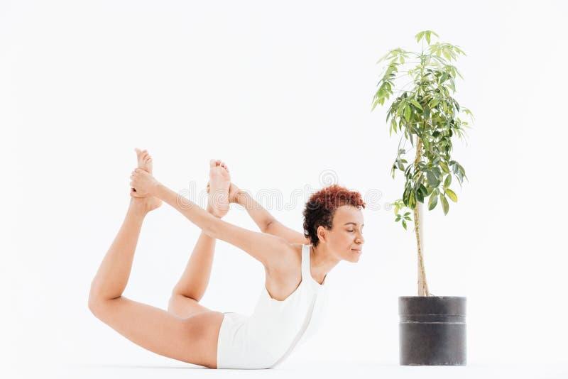 Öva för kvinna för nätt afrikansk amerikan ungt och praktiserande yoga royaltyfri bild